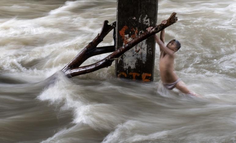 当地时间2018年6月11日,菲律宾马尼拉,儿童在暴雨后桥下暴涨的河水中玩耍(供图 视觉中国).jpg