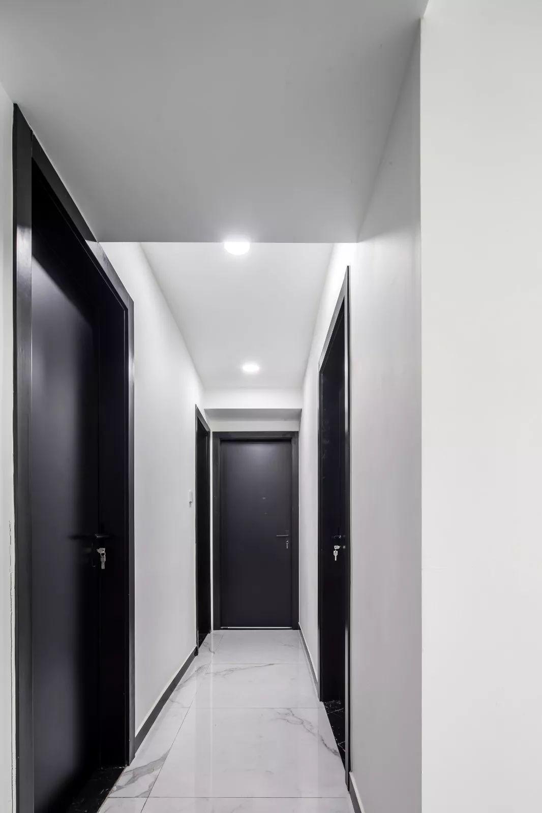 走廊雅致的白色大理石地砖,纯净的墙面,搭配黑色房间门,简洁又时尚.